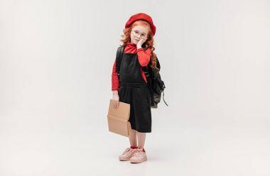 adorable little schoolgirl with backpack and big book isolated on grey
