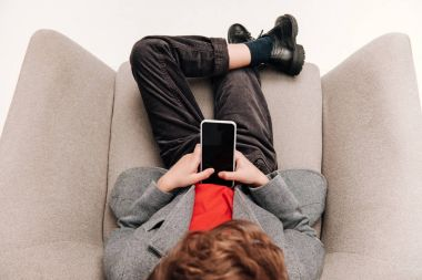 top view of stylish little boy using smartphone in armchair
