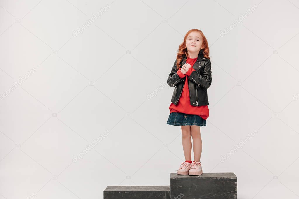 adorable little girl in leather jacket on wooden box isolated on grey