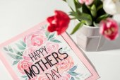 Detailní pohled šťastné matky den karty a tulipány ve váze na bílém