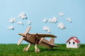 Photo close-up view of wooden toy plane on green grass and blue sky with clouds