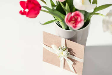 selective focus of beautiful blooming tulip flowers in vase and envelope on grey