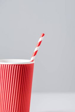 close-up view of red paper cup with drinking straw isolated on grey