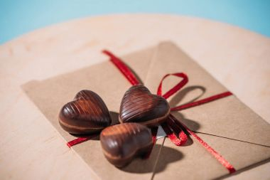 close-up view of heart shaped chocolate candies on envelope with red ribbon, selective focus with copy space
