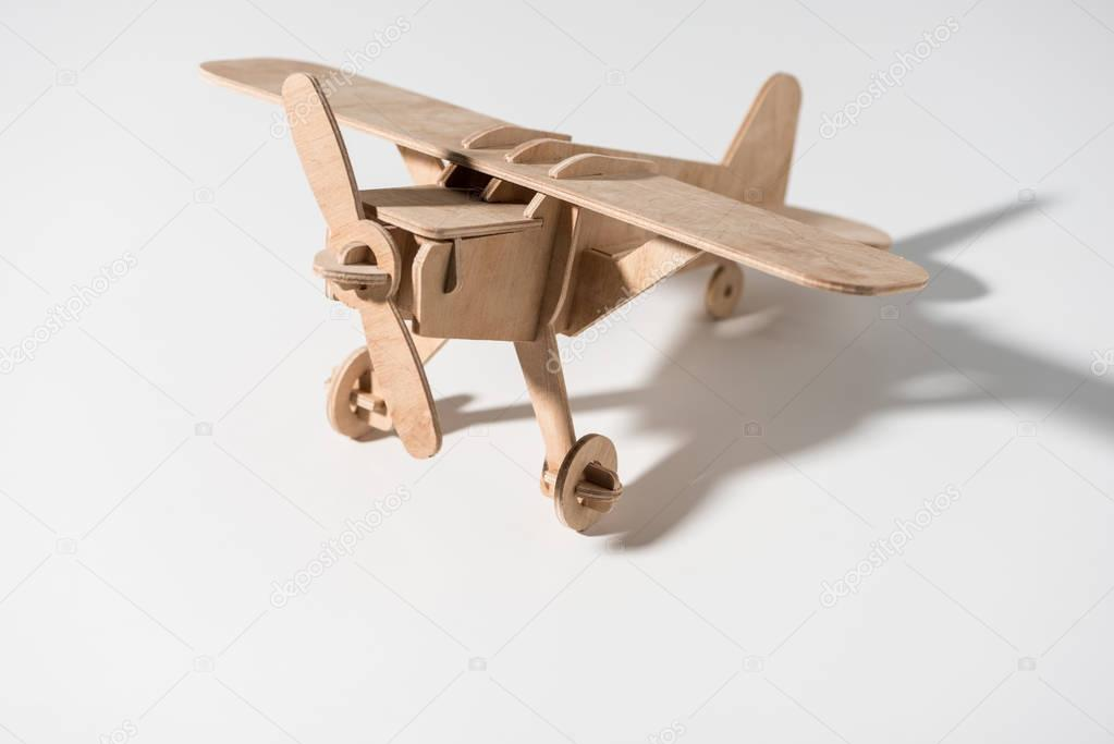 close-up view of small wooden toy plane on white