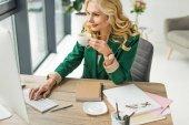 usměvavá podnikatelka pomocí stolního počítače a pití kávy na pracovišti