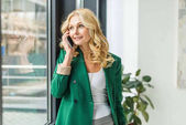 smiling businesswoman talking by smartphone and looking at window
