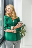 pensive businesswoman holding smartphone and looking at window