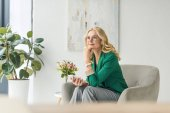 Photo pensive businesswoman in eyeglasses holding smartphone and looking away