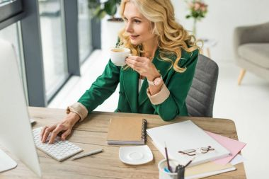smiling businesswoman using desktop computer and drinking coffee at workplace
