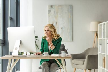 middle aged businesswoman using desktop computer and drinking coffee at workplace