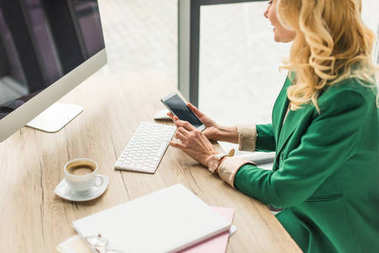 cropped shot of businesswoman using smartphone at workplace
