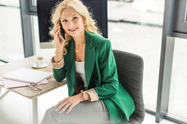 beautiful middle aged businesswoman talking on smartphone and smiling at camera