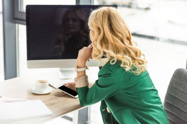 businesswoman using smartphone and desktop computer with blank screen at workplace