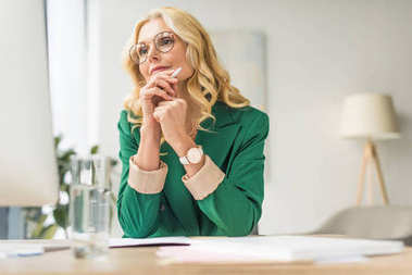 mature businesswoman in eyeglasses holding pen and using desktop computer at workplace