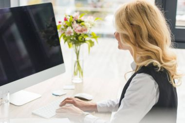 attractive mature businesswoman using desktop computer at workplace