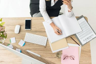 high angle view of businesswoman doing paperwork at workplace