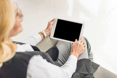 selective focus of businesswoman in eyeglasses using digital tablet with blank screen