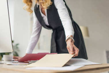 selective focus of businesswoman holding envelope at workplace