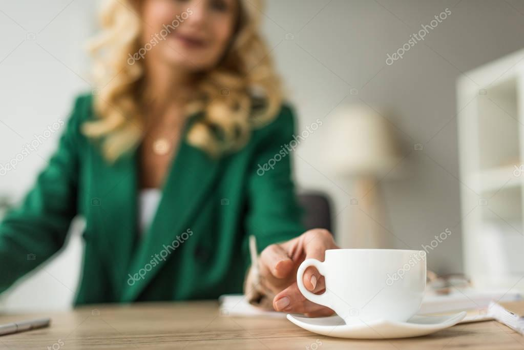 close-up partial view of businesswoman holding cup of coffee at workplace