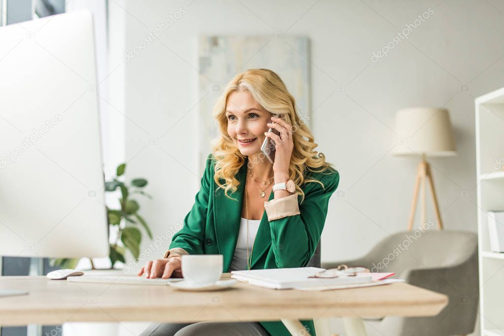 attractive smiling mature businesswoman using smartphone and desktop computer at workplace