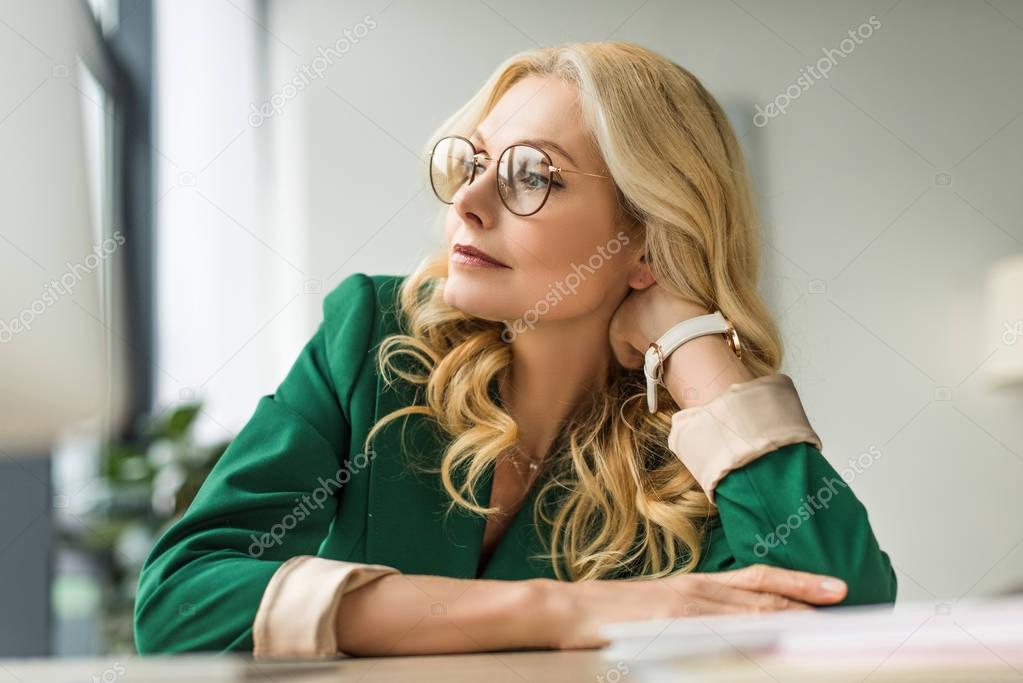 portrait of beautiful pensive middle aged businesswoman in eyeglasses looking away