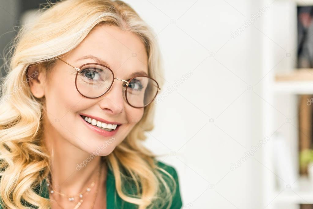 close-up portrait of beautiful mature businesswoman in eyeglasses smiling at camera