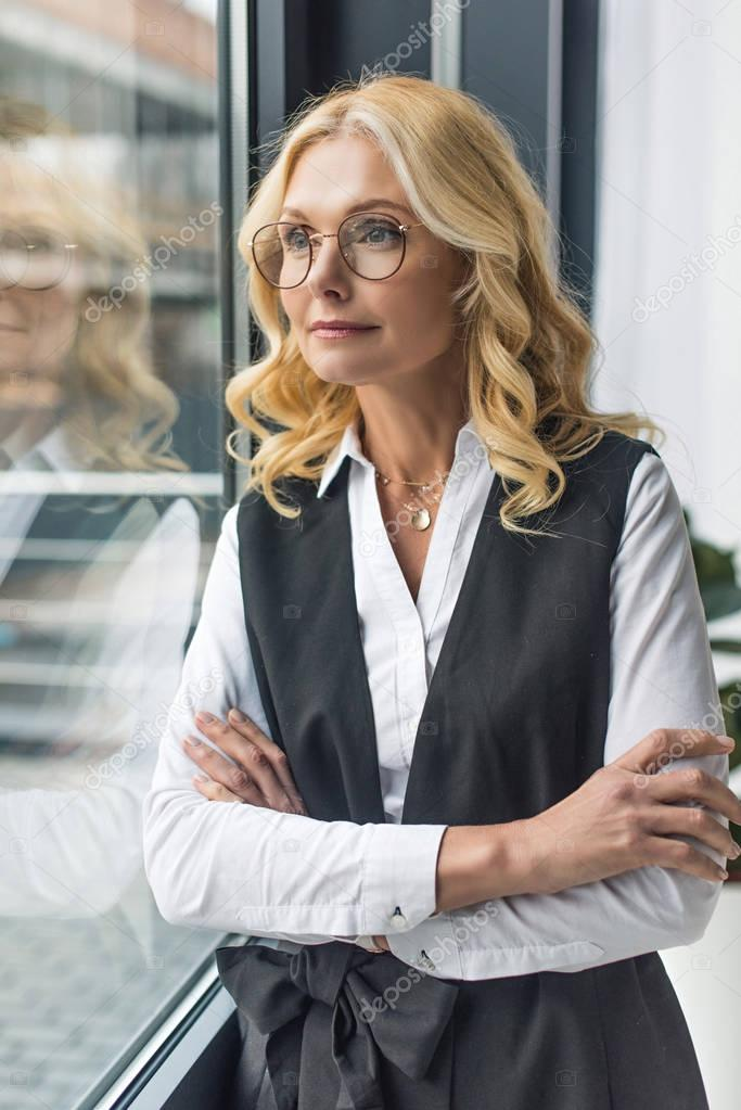 portrait of beautiful middle aged businesswoman with crossed arms looking at window