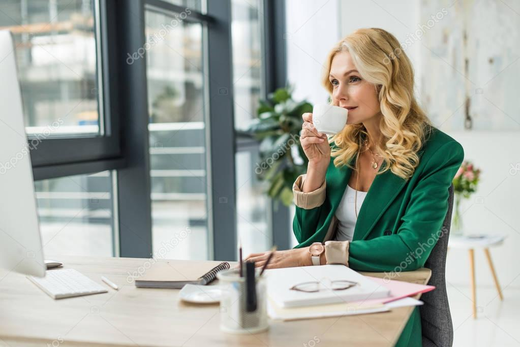businesswoman drinking coffee and using desktop computer at workplace