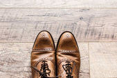 Photo top view of pair of leather brown shoes on wooden floor