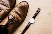 top view of brown shoes and watch on wooden surface