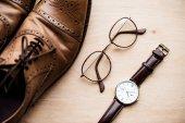 pohled shora hnědé boty, brýle a hodinky na dřevěný povrch
