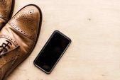 pohled shora na smartphone a hnědé kožené boty na dřevěný povrch
