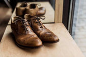 Photo modern brown male shoes at showcase in shop