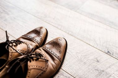 pair of leather brown shoes on wooden floor