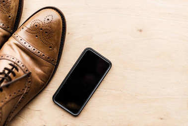 top view of smartphone and brown leather shoes on wooden surface