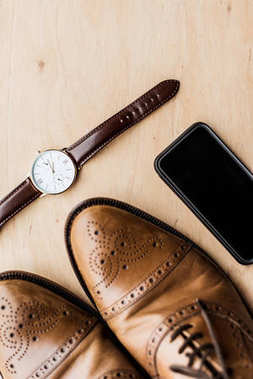 top view of watch, smartphone and shoes on wooden table