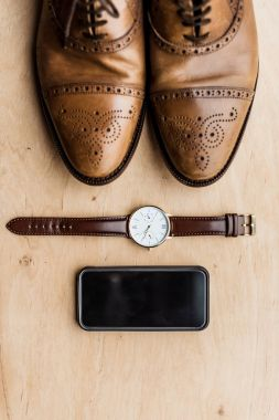 top view of shoes, smartphone and watch on wooden surface