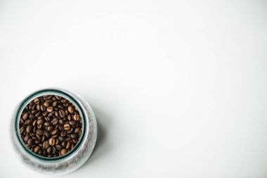 Top view of glass bottle with coffee beans on white stock vector