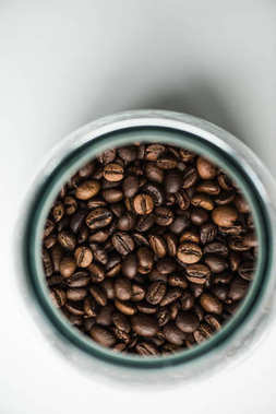 top view of glass bottle with coffee beans on white