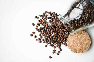 Top view of scattered coffee beans from glass bottle and cork isolated on white stock vector