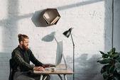 a jóképű üzletember számítógép hivatalban dolgozó oldalnézete