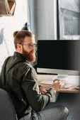 Fotografie bärtige Geschäftsmann hält Tasse Kaffee im Büro