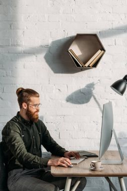side view of handsome businessman working with computer in office