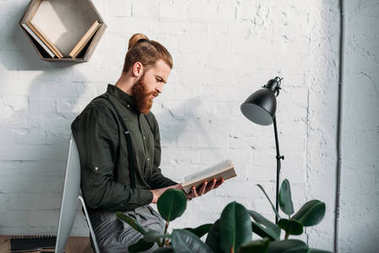 side view of handsome bearded businessman sitting on table and reading book