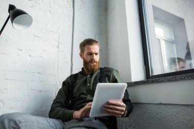 bearded businessman using tablet in office