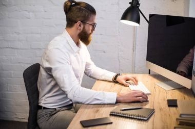 businessman typing something on keyboard in office