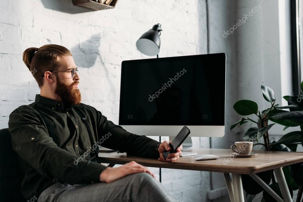 handsome businessman sitting, holding smartphone and looking away
