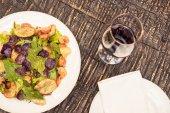 Fotografie lahodný salát s vínem na rustikální dřevěný stůl