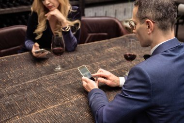 unhappy adult couple using smartphones on date at restaurant